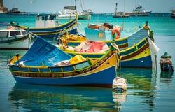 Les bateaux de pêche s'approchent du village de Marsaxlokk Photographie stock