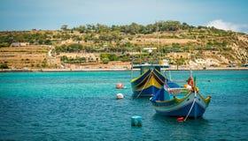Les bateaux de pêche s'approchent du village de Marsaxlokk Photo stock