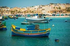 Les bateaux de pêche s'approchent du village de Marsaxlokk Photographie stock libre de droits