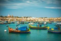 Les bateaux de pêche s'approchent du village de Marsaxlokk Photos stock