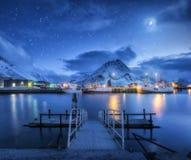 Les bateaux de pêche s'approchent de la jetée sur la mer et des montagnes neigeuses la nuit Photos libres de droits