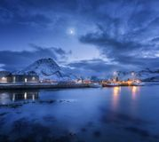 Les bateaux de pêche s'approchent de la jetée sur la mer et des montagnes neigeuses la nuit Photographie stock libre de droits