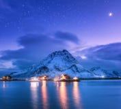 Les bateaux de pêche s'approchent de la jetée sur la mer et des montagnes neigeuses la nuit Images libres de droits