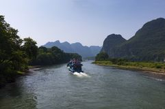 Les bateaux de passager avec des touristes dans Li River avec la chaux grande fait une pointe à l'arrière-plan près de Yangshuo e Photographie stock