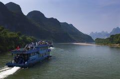 Les bateaux de passager avec des touristes dans Li River avec la chaux grande fait une pointe à l'arrière-plan près de Yangshuo e Photographie stock libre de droits