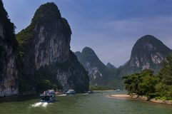 Les bateaux de passager avec des touristes dans Li River avec la chaux grande fait une pointe à l'arrière-plan près de Yangshuo e Photo stock