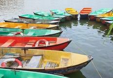 Les bateaux de rangée colorés multi ont amarré dans un lac Photographie stock