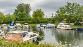 Les bateaux des types et des tailles différents rayent les banques de la rivière grand Ouse en Ely images stock