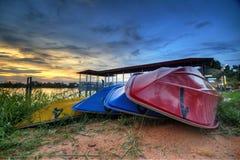 Les bateaux empilent à la berge avec le fond de coucher du soleil Image libre de droits
