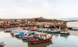 Les bateaux et les bateaux ont amarré dans un petit port, dans la pierre de fond Photos stock