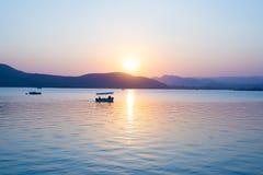 Les bateaux flottant sur le lac Pichola avec le coucher du soleil coloré ont relancé sur le beyong de l'eau les collines Udaipur, Image stock