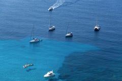 Les bateaux ont ancré outre de la côte sur la mer calme bleue images libres de droits