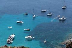 Les bateaux ont ancré outre de la côte sur la mer calme bleue photo libre de droits
