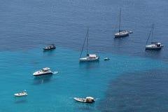 Les bateaux ont ancré outre de la côte sur la mer calme bleue images stock