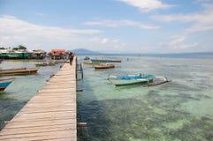 Les bateaux s'approchent du long pilier de bois de construction de village Image libre de droits