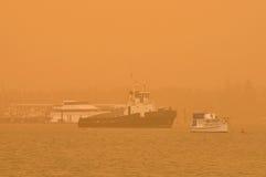 Les bateaux se trouvent au point d'attache dans une tempête de poussière au-dessus de l'océan Images stock