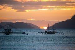 Les bateaux silhouettent en mer sur le coucher du soleil et le fond d'?les r images libres de droits