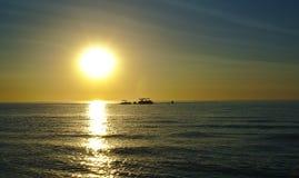 Les bateaux silhouettent pendant le coucher du soleil sur la plage images libres de droits