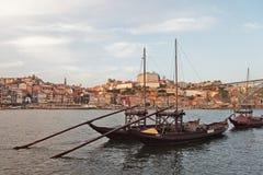 Les bateaux traditionnels avec des barils de vin avec la m?tro s'exercent sur le pont de Dom Luis et la ville de Porto ? l'arri?r photo libre de droits