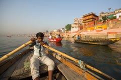 Les bateliers sur un bateau glisse par l'eau sur le Gange le long du rivage de Varanasi Photos stock
