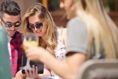 Les beaux amis élégants utilisent un comprimé numérique, café potable et sourient tout en se reposant en parc Image stock