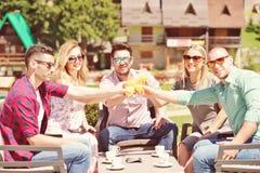 Les beaux amis élégants utilisent un comprimé numérique, café potable et sourient tout en se reposant en parc Images stock