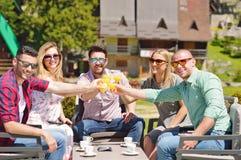 Les beaux amis élégants utilisent un comprimé numérique, café potable et sourient tout en se reposant en parc Photographie stock