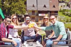 Les beaux amis élégants utilisent un comprimé numérique, café potable et sourient tout en se reposant en parc Images libres de droits