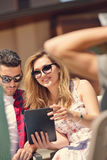 Les beaux amis élégants utilisent un comprimé numérique, café potable et sourient tout en se reposant en parc Photo libre de droits
