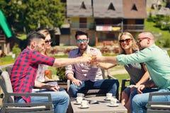 Les beaux amis élégants utilisent un comprimé numérique, café potable et sourient tout en se reposant en parc Photographie stock libre de droits