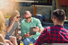 Les beaux amis élégants utilisent un comprimé numérique, café potable et sourient tout en se reposant en parc Image libre de droits