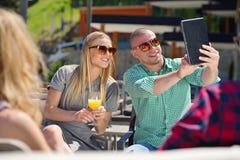 Les beaux amis élégants utilisent un comprimé numérique, café potable et sourient tout en se reposant en parc Photo stock