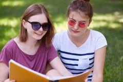 Les beaux amis féminins positifs ont concentré le regard dans le livre, découvrent le nouvel inforamtion utile, pose extérieure,  Photographie stock