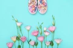 Les beaux chaussures en caoutchouc parmi l'eustoma fleurit sur le fond lumineux Photos stock