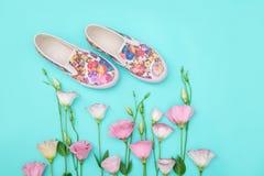 Les beaux chaussures en caoutchouc parmi l'eustoma fleurit sur le fond lumineux Photo libre de droits