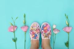 Les beaux chaussures en caoutchouc parmi l'eustoma fleurit sur le fond lumineux Image libre de droits