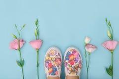 Les beaux chaussures en caoutchouc parmi l'eustoma fleurit sur le fond lumineux Photographie stock