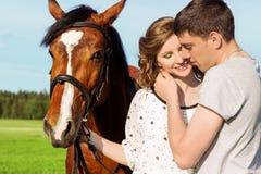 Les beaux couples affectueux des types et des filles dans le domaine marchent sur des chevaux Photographie stock