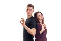 Les beaux couples affectueux tiennent des dos entre eux sourient et montrent des gestes de mains Okey Photo stock