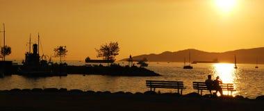 les beaux couples apprécient la vue de coucher du soleil de silhouette Images libres de droits