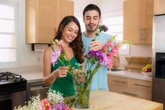 Les beaux couples dans des relations partagent des fleurs à la maison pendant l'été Photos stock
