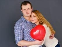 Les beaux couples dans l'amour avec le coeur rouge de ballon forment pour le jour de valentine, sur le fond gris Image libre de droits