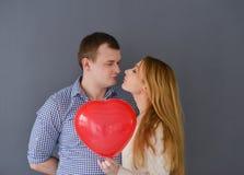 Les beaux couples dans l'amour avec le coeur rouge de ballon forment pour le jour de valentine, sur le fond gris Photo stock