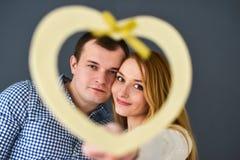Les beaux couples dans l'amour avec le coeur rouge forment pour le jour de valentine, sur le fond gris Photos stock