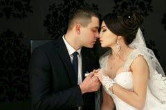Les beaux couples dans l'amour embrassant près du mur Photos stock