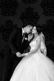 Les beaux couples dans l'amour embrassant près du mur Image libre de droits