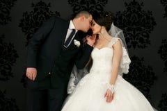 Les beaux couples dans l'amour embrassant près du mur Photos libres de droits