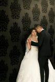 Les beaux couples dans l'amour embrassant près du mur Image stock