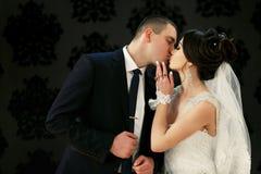 Les beaux couples dans l'amour embrassant près du mur Photographie stock libre de droits