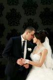 Les beaux couples dans l'amour embrassant près du mur Photo stock